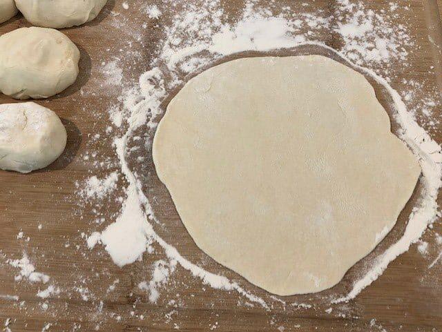 Use Rolling Pin To Flatten Tortilla Dough Ball into Flat Circles